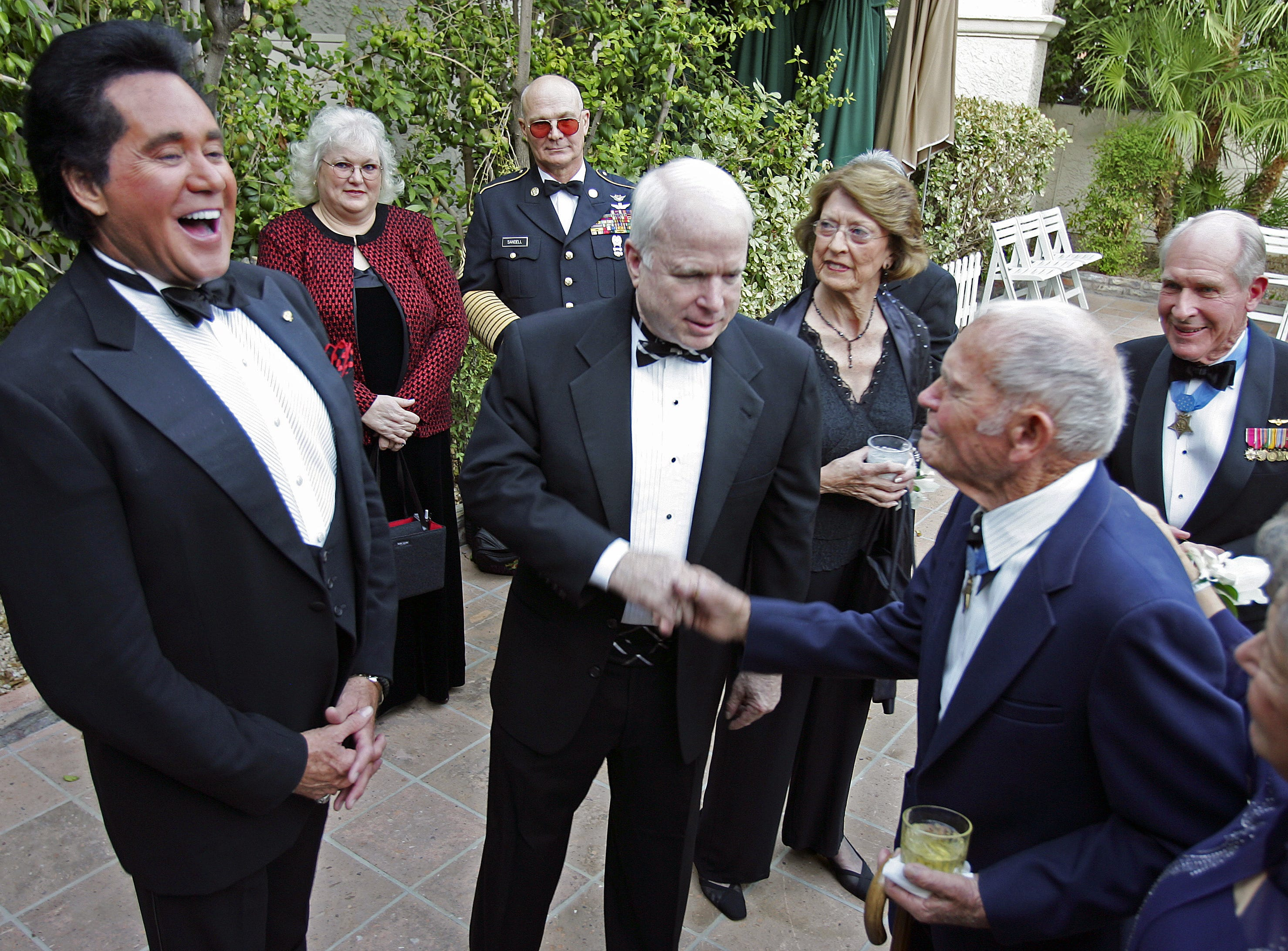 Medal of Honor recipient John Finn (right) shakes hands with Sen. John McCain while Wayne laughs at an award reception and dinner  at the Pointe Hilton Tapatio Cliffs in Phoenix on Sept. 30, 2005.