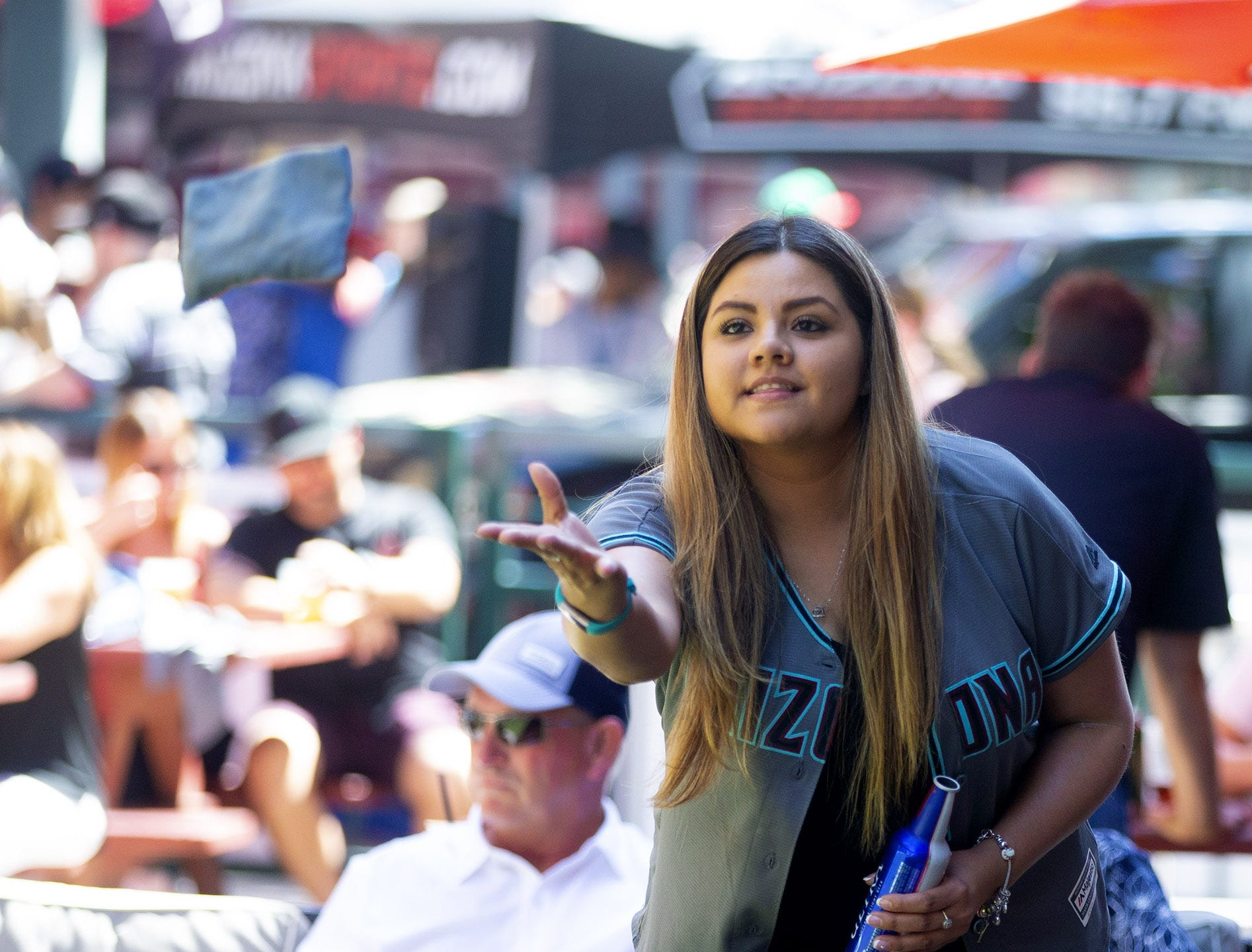 Roxanna Higuera, from Douglas, plays corn hole during Opening Day street festival at Chase Field in Phoenix on April 5.