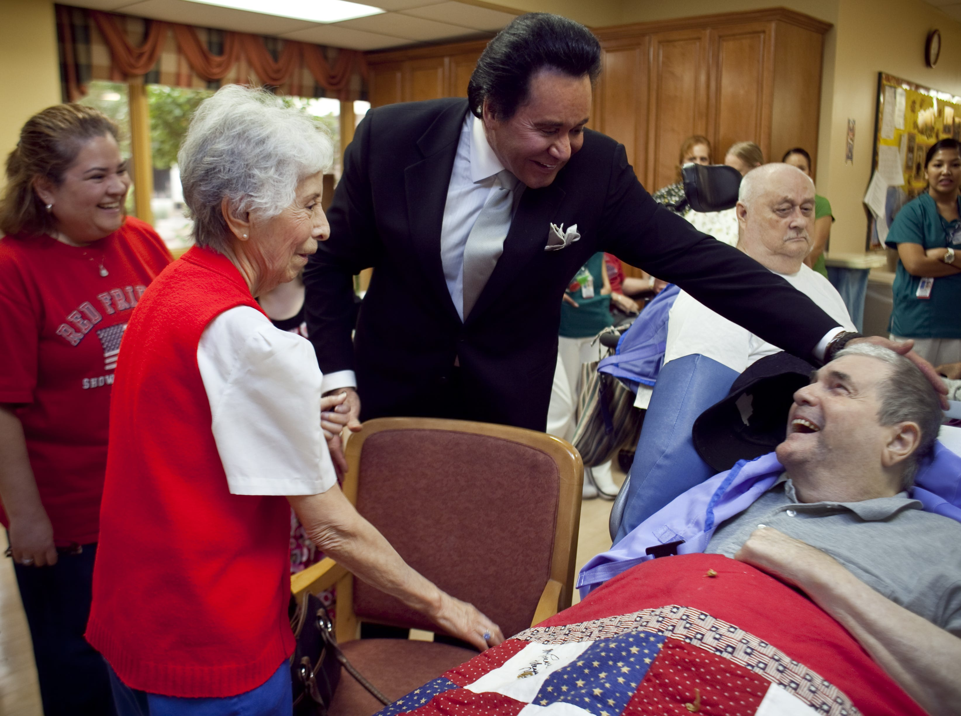 Wayne Newton greets veteran Hurlie Cook during a visit to the VA Community Living Center in 2009.  Looking on is Cook's daughter, Teresa Privette (left) and his wife, Lydia Cook.
