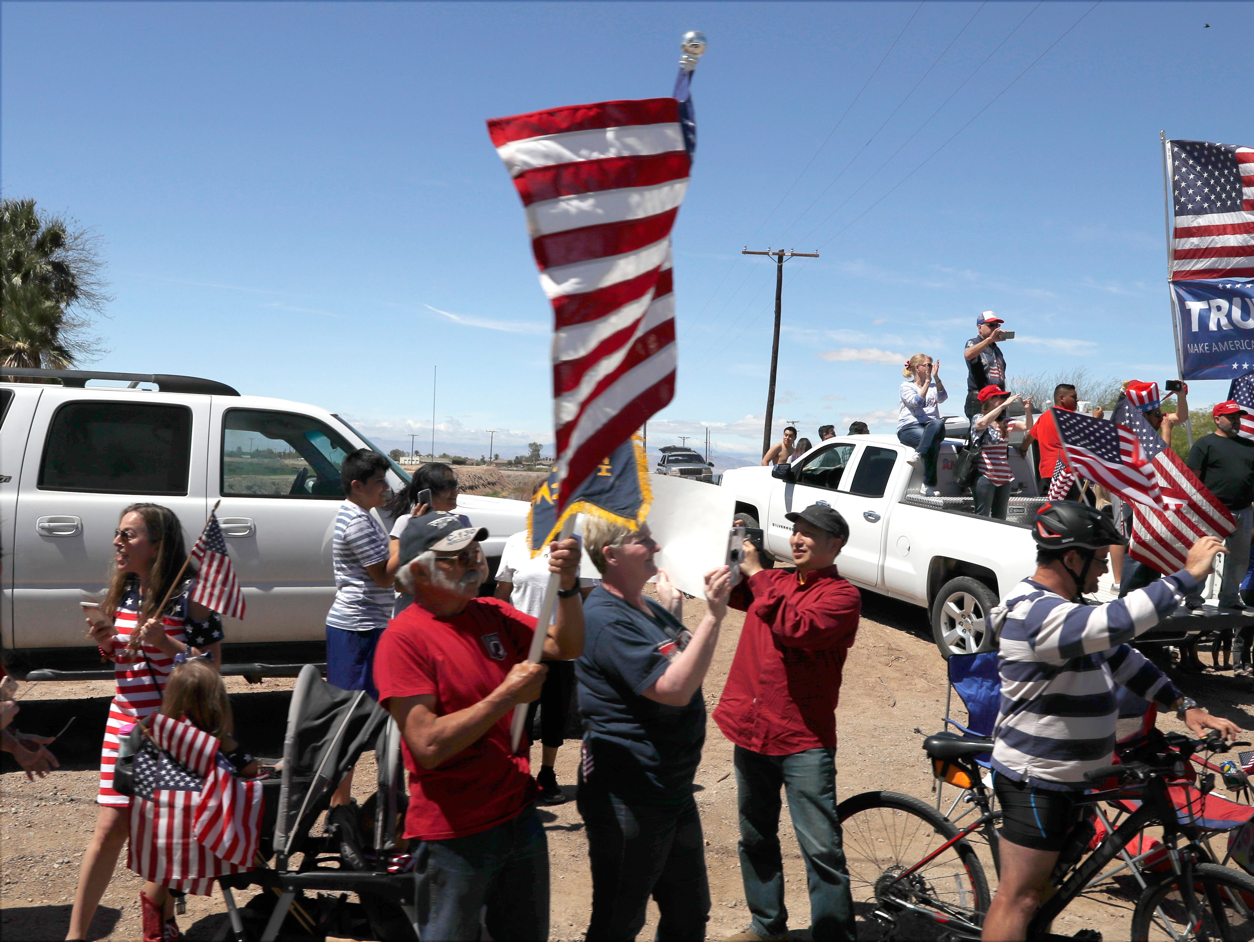 People line the street in El Centro, California, April 5, 2019, as President Donald Trump headed to the border with Mexico to make a renewed push for border security as a central campaign issue for his 2020 re-election.