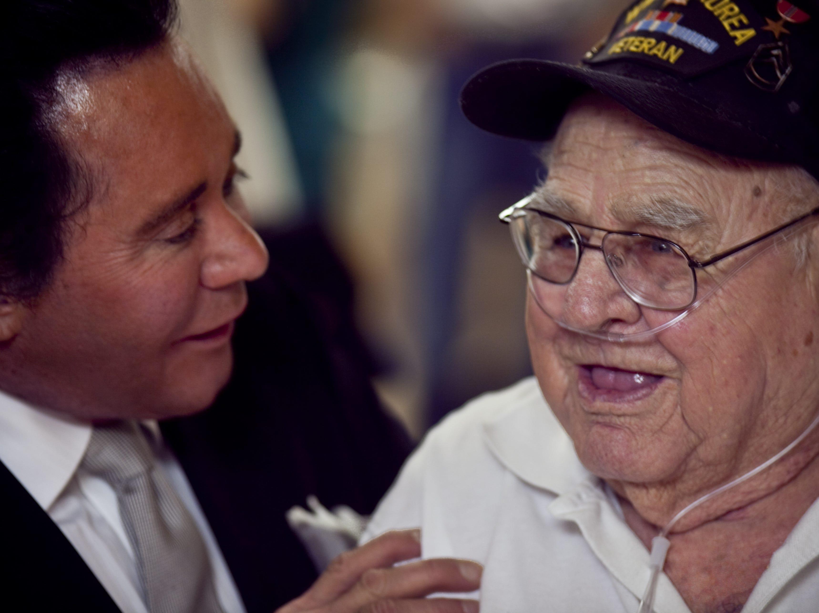 Wayne Newton (left) greets Ira Kile, a veteran of World War II and the Korean War, during a 2009 visit to the VA Community Living Center in Phoenix.