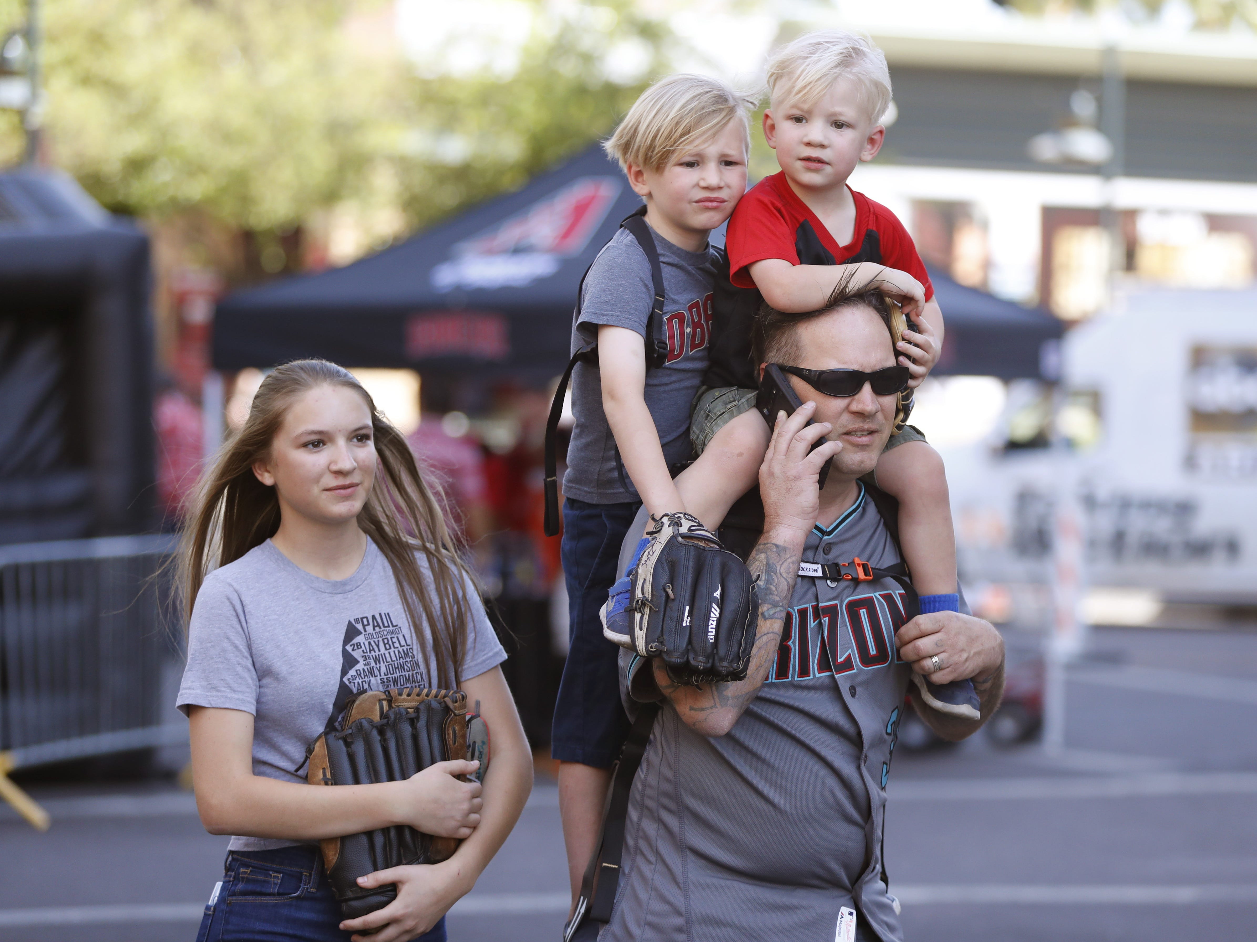 Patrick Flannagan holds his sons Liam (R) and Finn on his back as they make their way outside Chase Field with Patrick's daughter Cat on the Opening Day for the Diamondbacks in Phoenix, Ariz. on April 5, 2019.