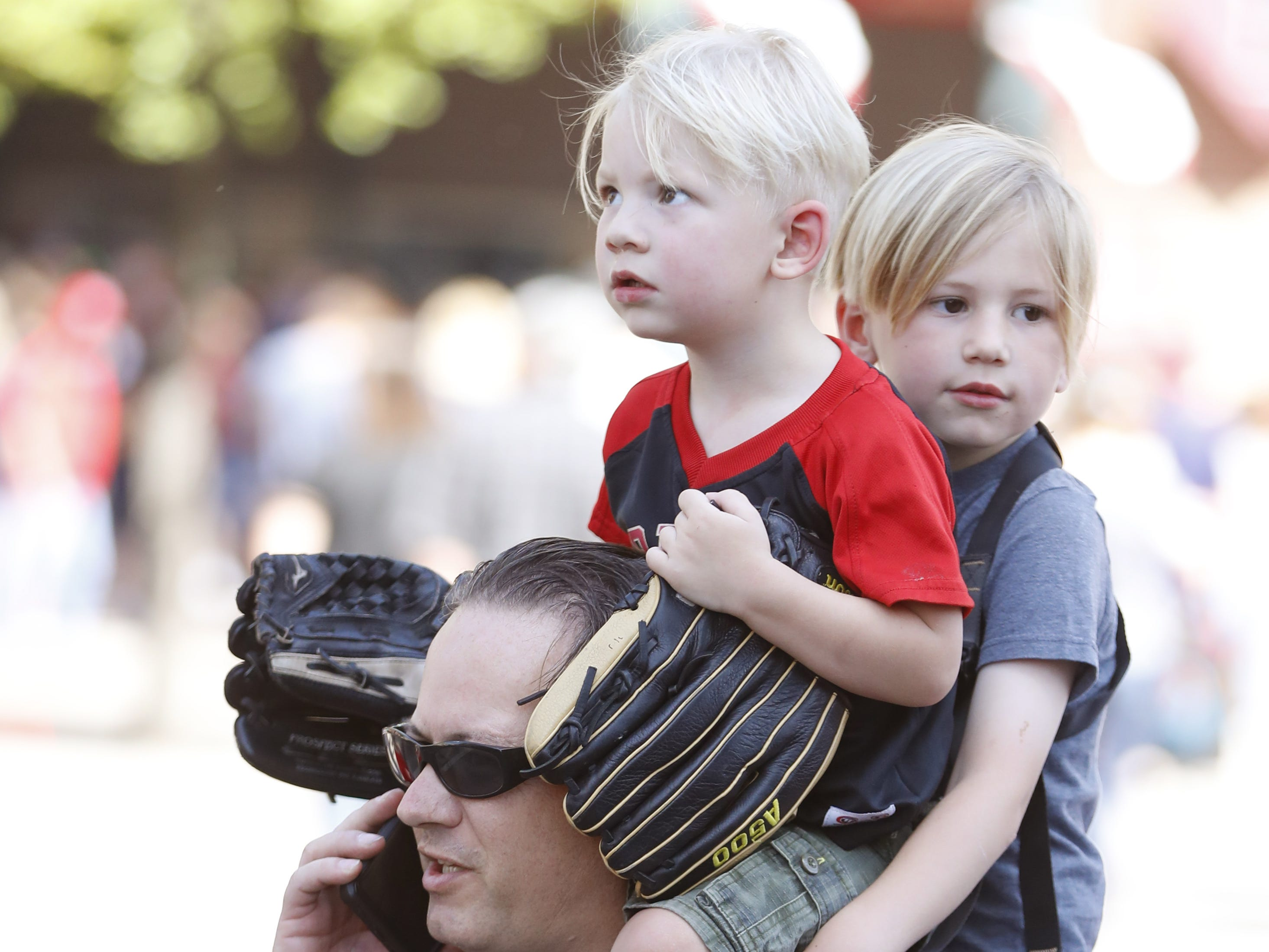 Patrick Flannagan holds his sons Liam (R) and Finn on his back as they make their way outside Chase Field on the Opening Day for the Diamondbacks in Phoenix, Ariz. on April 5, 2019.