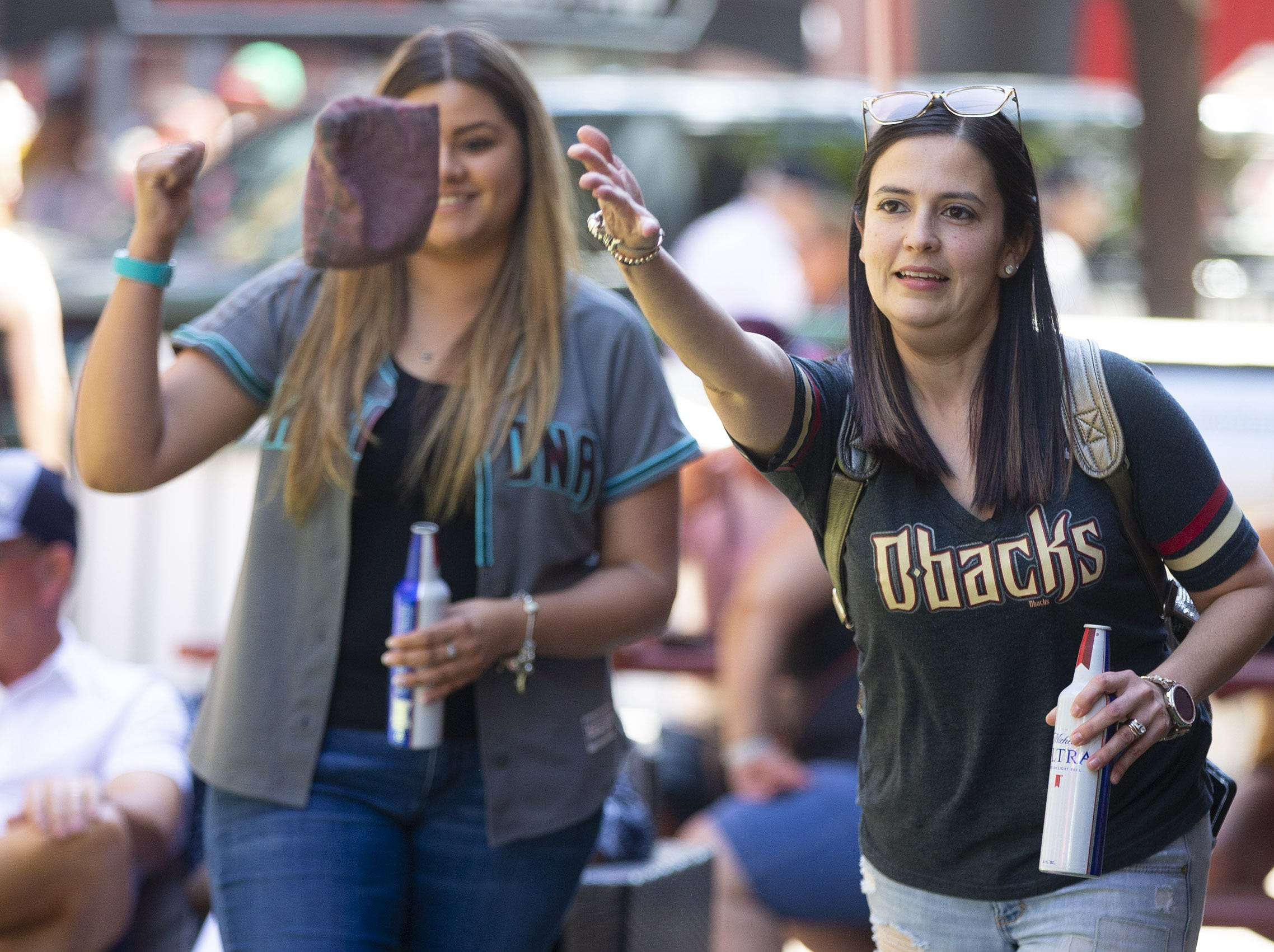 Roxanna Higuera, left,  and Erika Cuevas, from Douglas, play corn hole during Opening Day street festival at Chase Field in Phoenix on April 5.