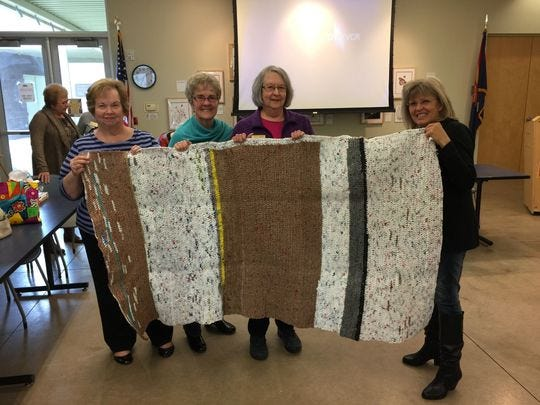 The GFWC (General Federation of Women's Clubs) Paradise Valley's Women Club made mats out of plastic bags for the homeless as a service project. This mat was made by Linda Nace (third from the left).