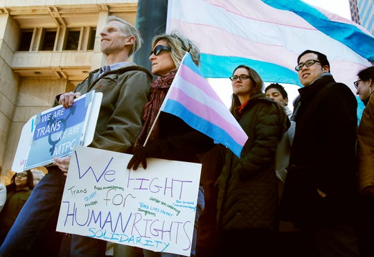 Eric and Evas Nelson, from Sandwich, Mass., and parents of a transgender child, wait for Boston Mayor Marty Walsh to arrive to raise a flag supporting the transgender community at City Hall, on March 30, 2017, in Boston.