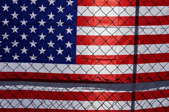 Una bandera americana con una cerca frente a ella.