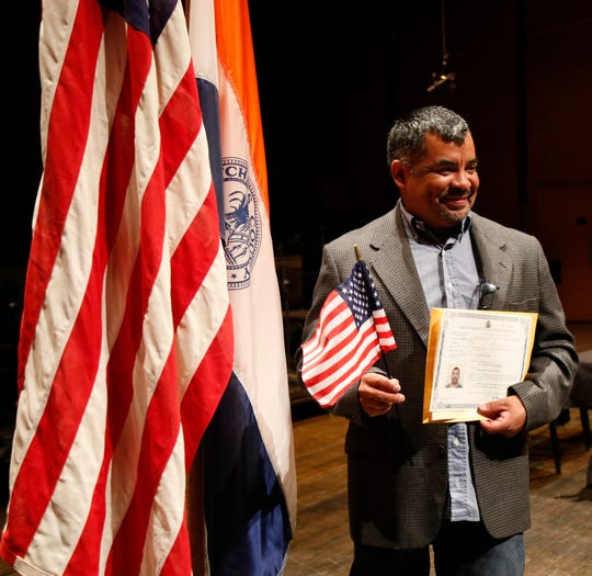 Julio A. DeLeon poses for a photo in front of the Dutchess County, New York State and  United States flags during the Dutchess County Naturalization Ceremony inside the Sosnoff Theater at Bard College on April 5, 2019.