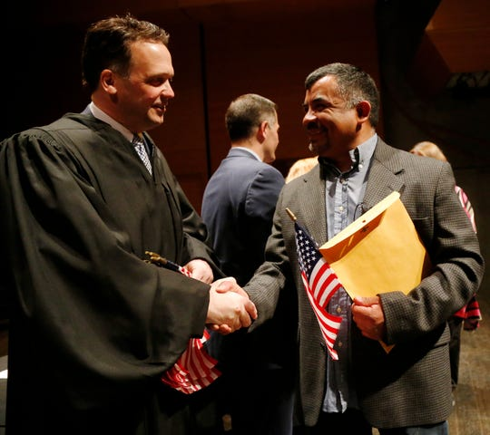 Dutchess County justice Edward McLoughlin congratulates Julio A. DeLeon on becoming a citizen during the Dutchess County Naturalization Ceremony inside the Sosnoff Theater at Bard College on April 5, 2019.