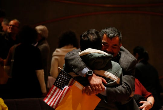 Julio A. DeLeon hugs his father Julio following the Dutchess County Naturalization Ceremony inside the Sosnoff Theater at Bard College on April 5, 2019.