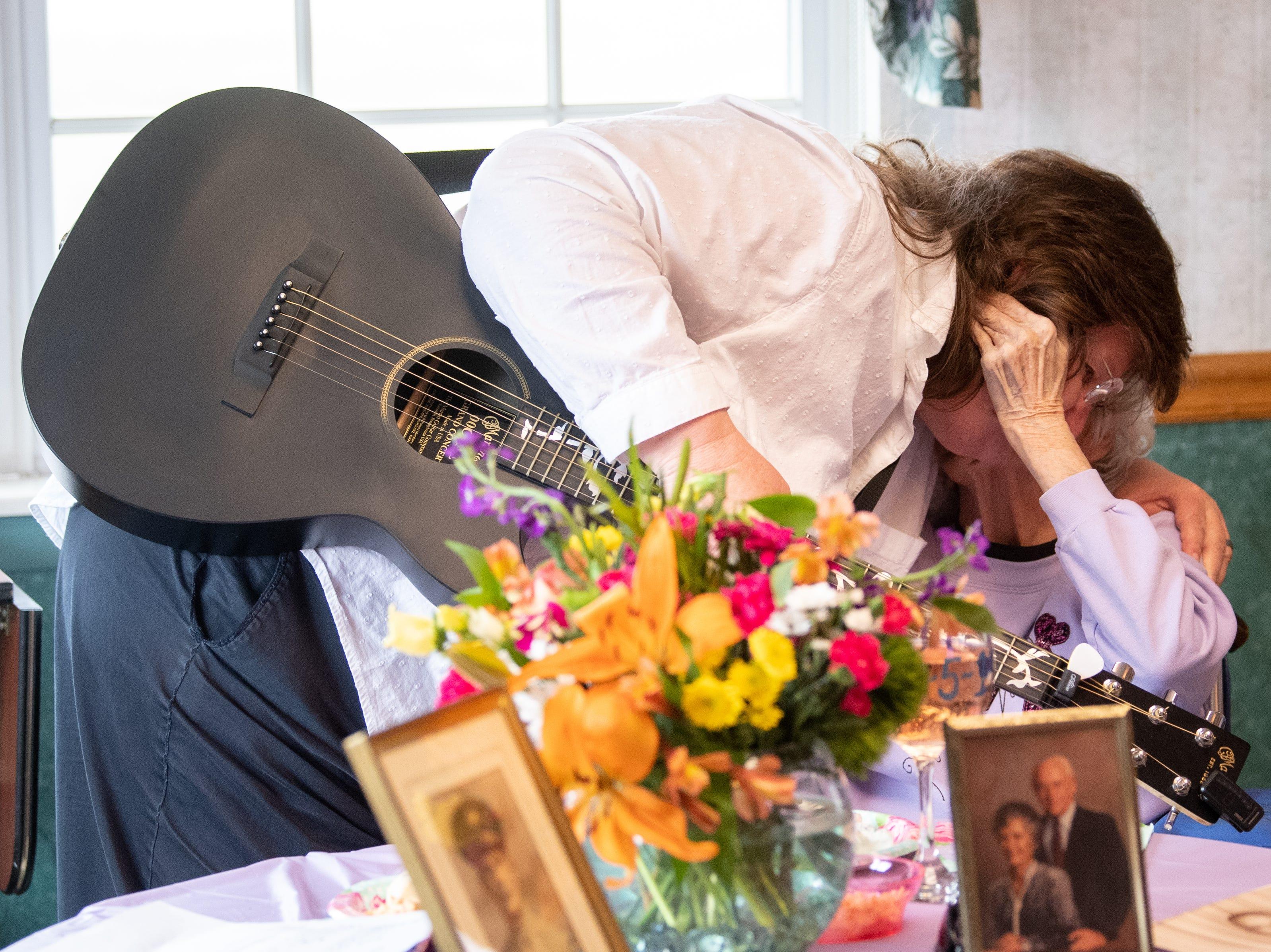 Spiritual Care Coordinator Margie Stevens gives Ann a hug after playing, April 5, 2019.