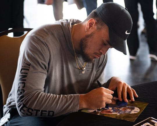 Penn State linebacker Koa Farmer signs a picture during the 55th Annual York Area Sports Night, April 4, 2019 at the Heritage Hills Golf and Conference Center.