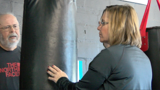 Lori DePorter, 50, holds the heavy bag for a student in the Rock Steady Boxing class at the Unique Physique gym in Springettsbury Township. DePorter's early on-set Parkinson's Disease diagnoses drove her beat back the disease with exercise ... and to help others do the same.