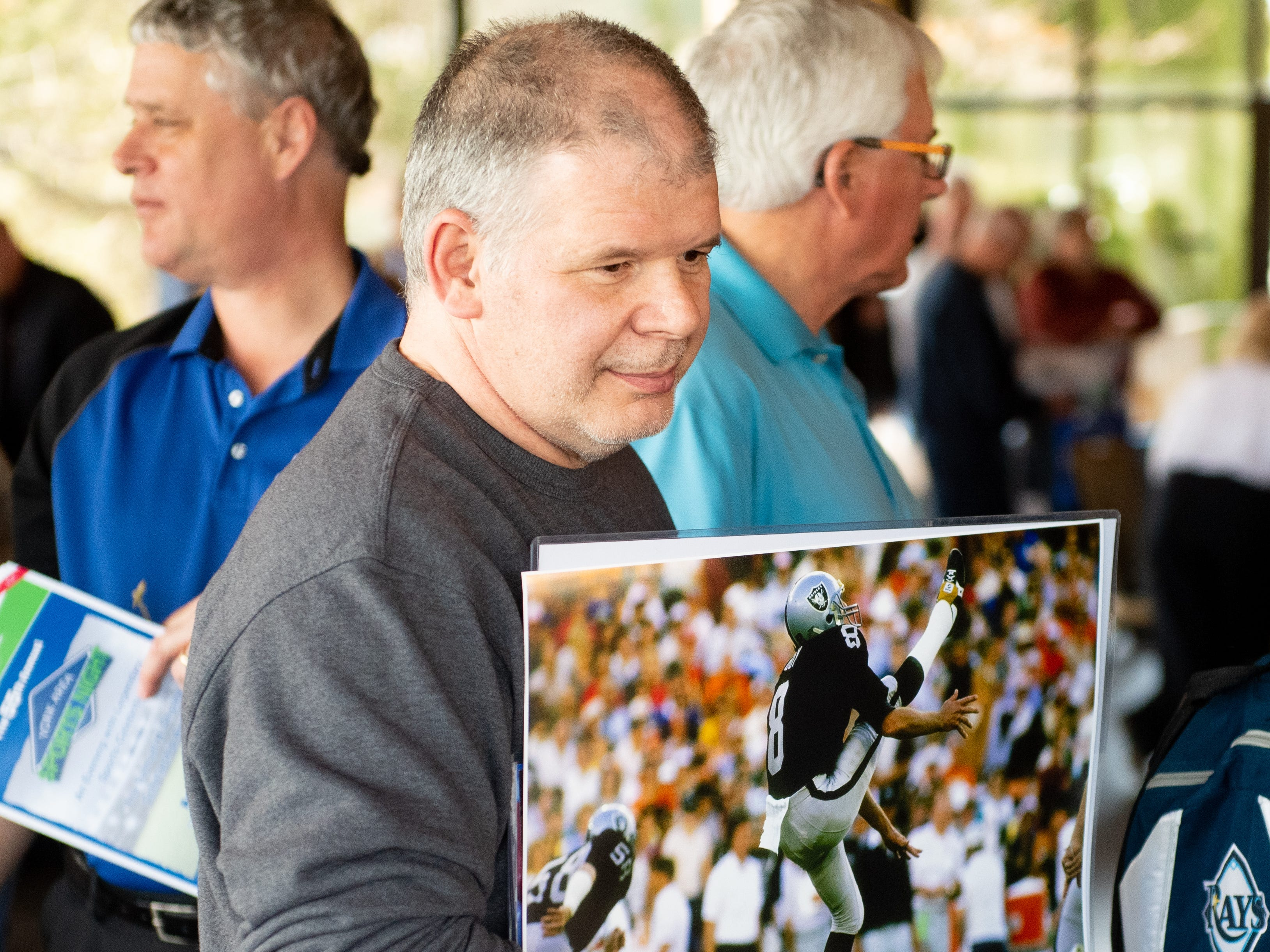 Darin Colp stands in line to meet hall of fame punter Ray Guy during the 55th Annual York Area Sports Night, April 4, 2019 at the Heritage Hills Golf and Conference Center.