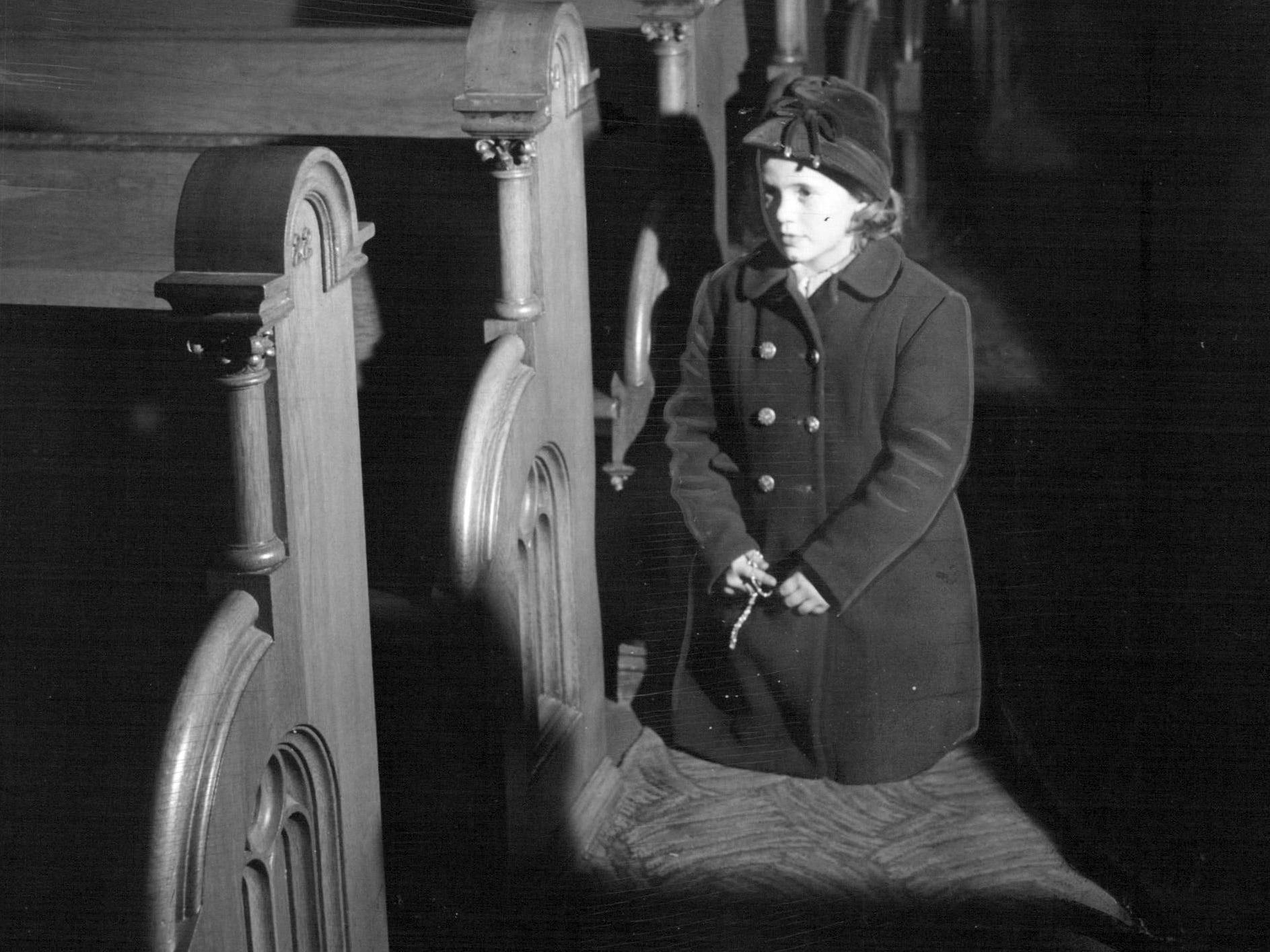 In this photo from 1955, Mary Ann Schulz, 6, kneel in reverence in St. Mary's Church during the Lent season.
