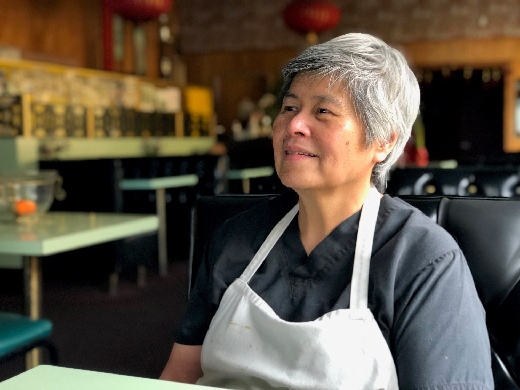 Jeannie Lim strikes a pensive pose in the dining room of her family's Chinese and American restaurant.