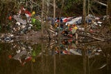 Josh Marthaller of West Salem boats on the Willamette Slough where trash and other items are piling up on the eastern banks south of downtown Salem.