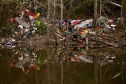 Trash can be seen from the Willamette Slough as items pile up along the banks south of downtown Salem on April 4, 2019.