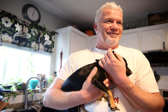 Chuck Hawley, of Silverton, holds Kylee, a miniature pinscher, who survived a rollover crash last month. She is now being taken care of thanks to the Sticky the Kitty Foundation, set up by the Hawley family after the kitten was found glued to the road in fall 2018. Photographed at the Hawley home on April 4, 2019.
