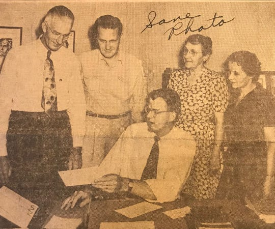The Rev. Morris Bratton, pastor of St. Luke Methodist Church, gingerly hands over a check for beginning of a building fund to Treasurer E.J. Darby as Mrs. H.C. DeShazo, teacher of the adult class, and Jeanette McClure, junior class teacher look on.