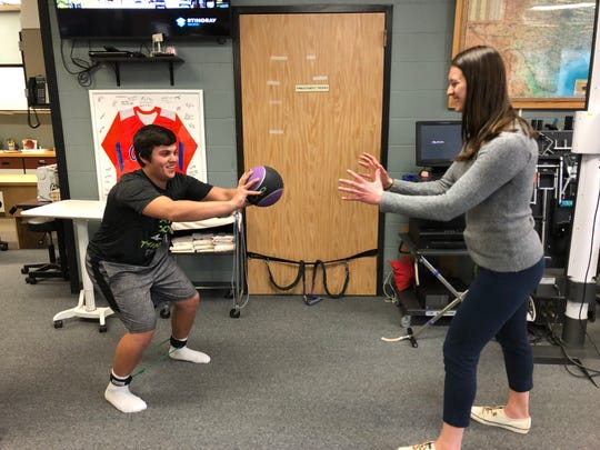 Jorian Fuentes, 17, completing rehab after a baseball injury  with Abby Beauchesne, occupational therapy student.
