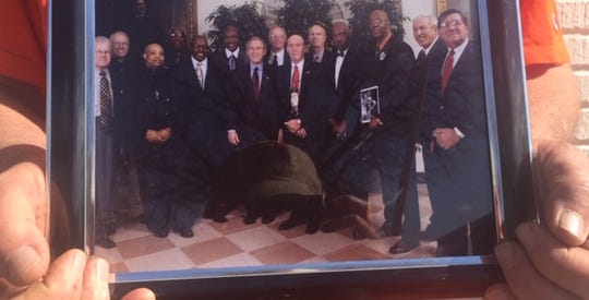 """Fred Schwake holds a photo of the 1966 Texas Western team during their 2006 visit to the White House to watch the movie """"Glory Road"""" with then-President George W. Bush."""