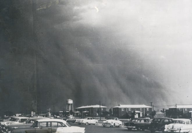 HERE IT COMES! —This impressive picture study was made shortly after 5 p.m. Wednesday as the menacing, reddish-brown clouds boiled nearer to San Angelo. the photo was made looking east across the Village Shopping Center south parking area. Moments later all of San Angelo was engulfed in stifling dust, motorists switched on their lights and fought to hold their cars in the street as winds up to 70 miles per hour buffeted the city.