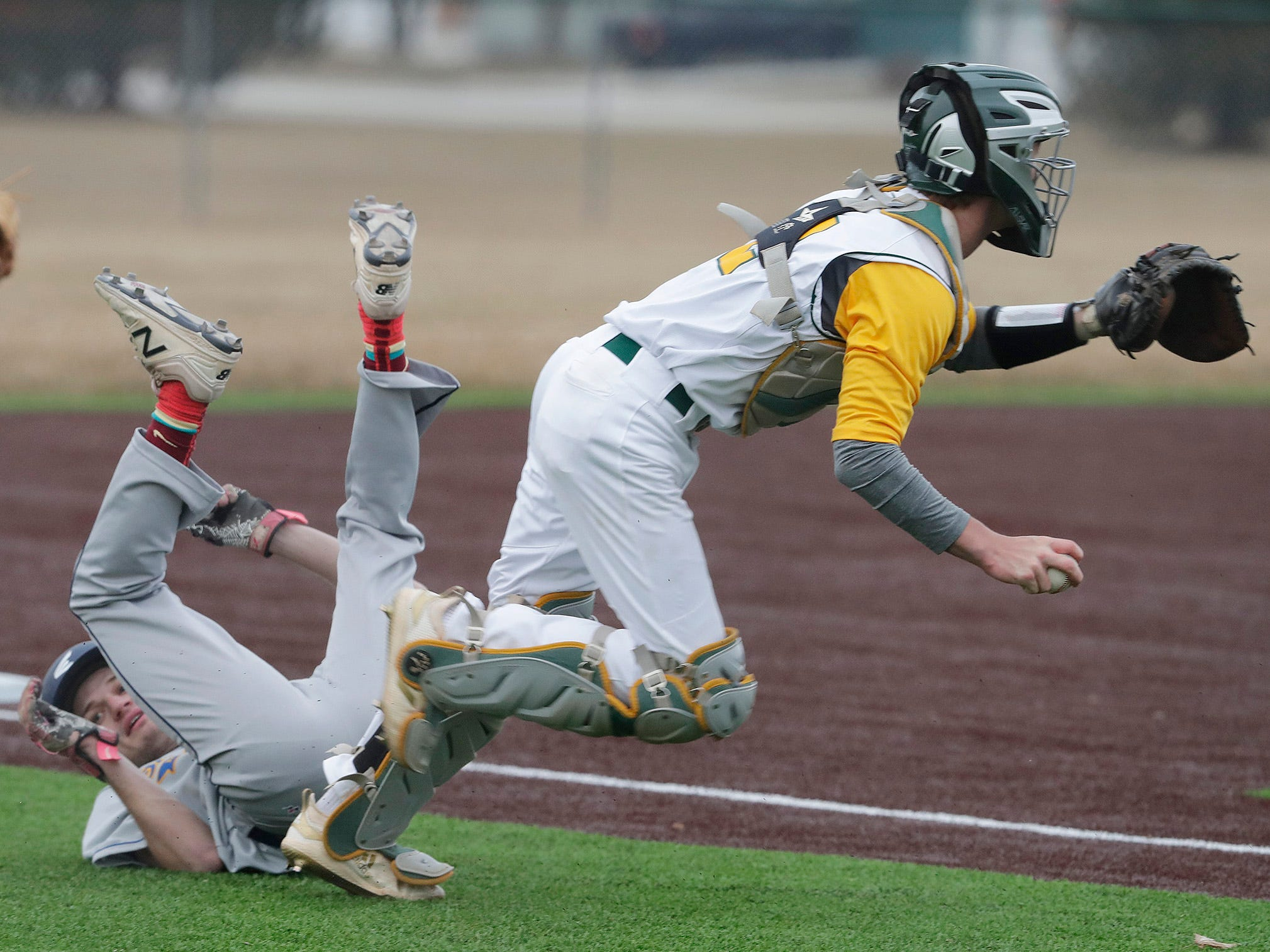 Sheboygan North's Ethan Scherg, left, rolls after being tagged out by Ashwaubenon's Brady Wittig, right, Thursday, April 4, 2019, in Sheboygan, Wis.