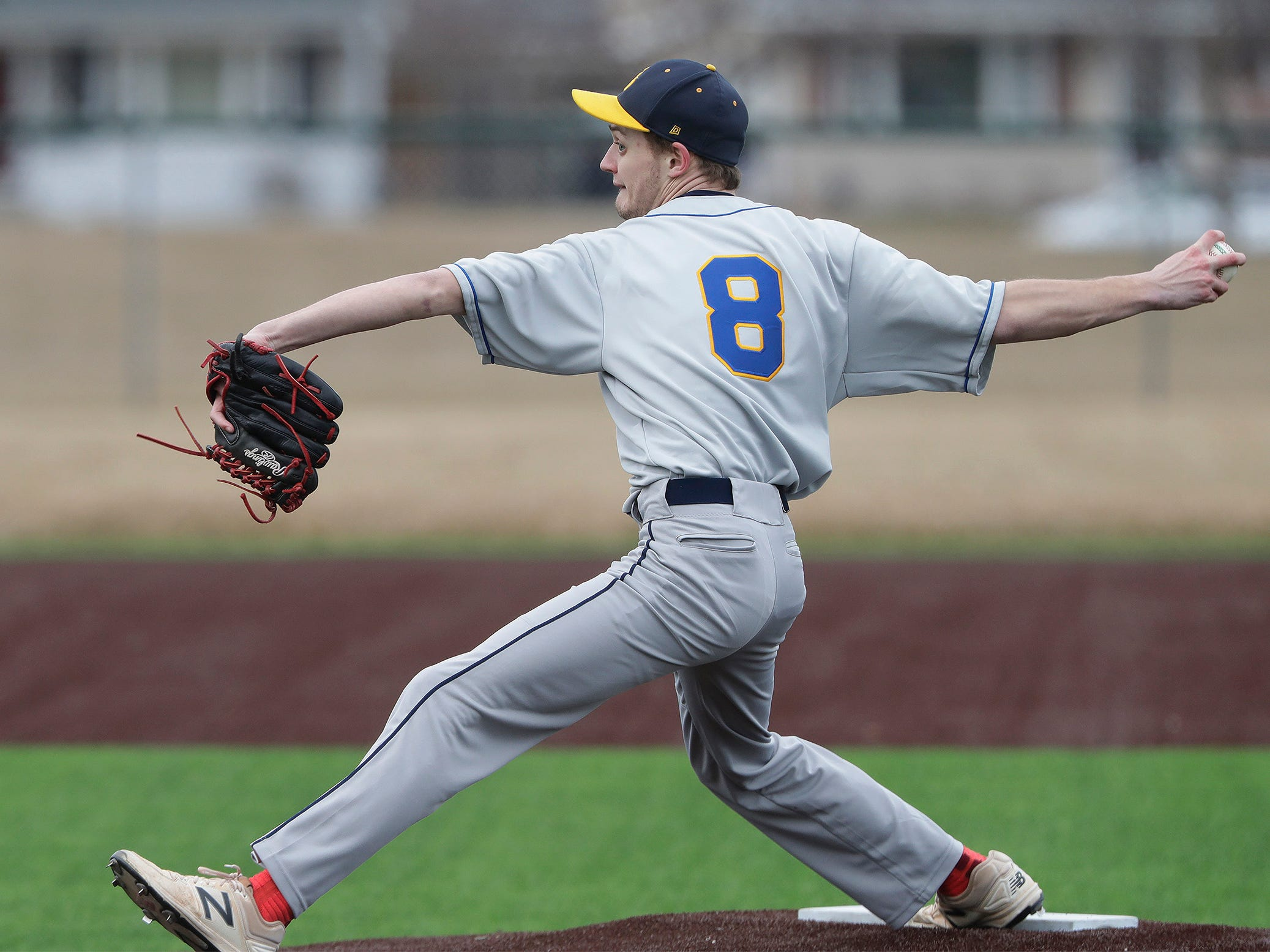 Sheboygan North's Ethan Scherg (8) winds up a pitch against Ashwaubenon, Thursday, April 4, 2019, in Sheboygan, Wis.