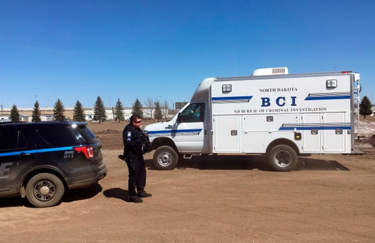 "In this Wednesday, April 3, 2019 photo, state and local police search a field in Manton, N.D., about half a mile from a business where an owner and three employees were found dead. Authorities on Thursday said they were looking for ""potential evidence"" related to the deaths discovered Monday at RJR Maintenance and Management in Mandan, a city just outside Bismarck. (AP Photo/ Blake Nicholson)"