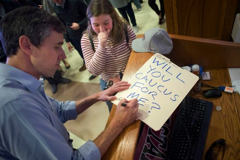 "Democratic presidential candidate and former Texas congressman Beto O'Rourke signs a sign that reads ""Will you caucus for me?"" after Claire Campbell of Sioux Falls, 17, asked him to be her prom date during a campaign event in Sioux City, Iowa, on Thursday, April 4, 2019. (Justin Wan/Sioux City Journal via AP)"