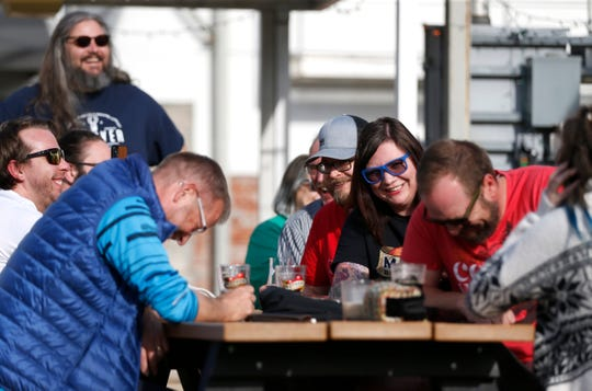 Mother's Brewery employees and patrons laugh during a eulogy for Towhead, an American blonde lager that the brewery is discontinuing at a ceremonial farewell on Friday, April 5, 2019.