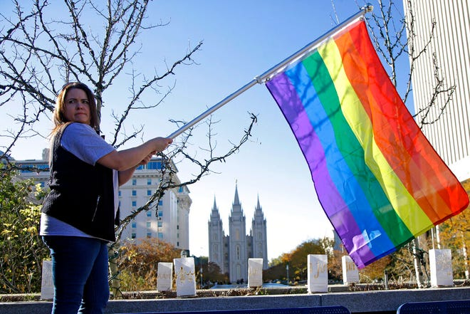 FILE - In this Nov. 14, 2015 file photo, Sandy Newcomb poses for a photograph with a rainbow flag as people gather for a mass resignation from The Church of Jesus Christ of Latter-day Saints in Salt Lake City. The Church of Jesus Christ of Latter-day Saints is repealing rules unveiled in 2015 that banned baptisms for children of gay parents and made gay marriage a sin worthy of expulsion. The surprise announcement Thursday, April 4, 2019, by the faith widely known as the Mormon church reverses rules that triggered widespread condemations from LGBTQ members and their allies. (AP Photo/Rick Bowmer, File)
