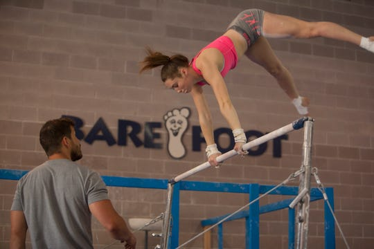 Bare Foot's Sarah Brown,  here on the uneven bars being coached by Caleb Phillips, is a level 10 gymnast who fell in love with gymnastics after her mother put her in the sport.