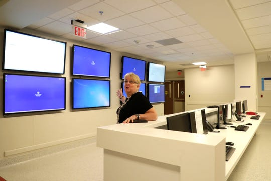 Linda Fox, service line administrator for surgical services, details the importance of the eight large monitors at a nurses station in the M.T. Mustian Center at Tallahassee Memorial Hospital Friday, April 5, 2019. The monitors are used to track a patient's progress through pre-operation to recovery.