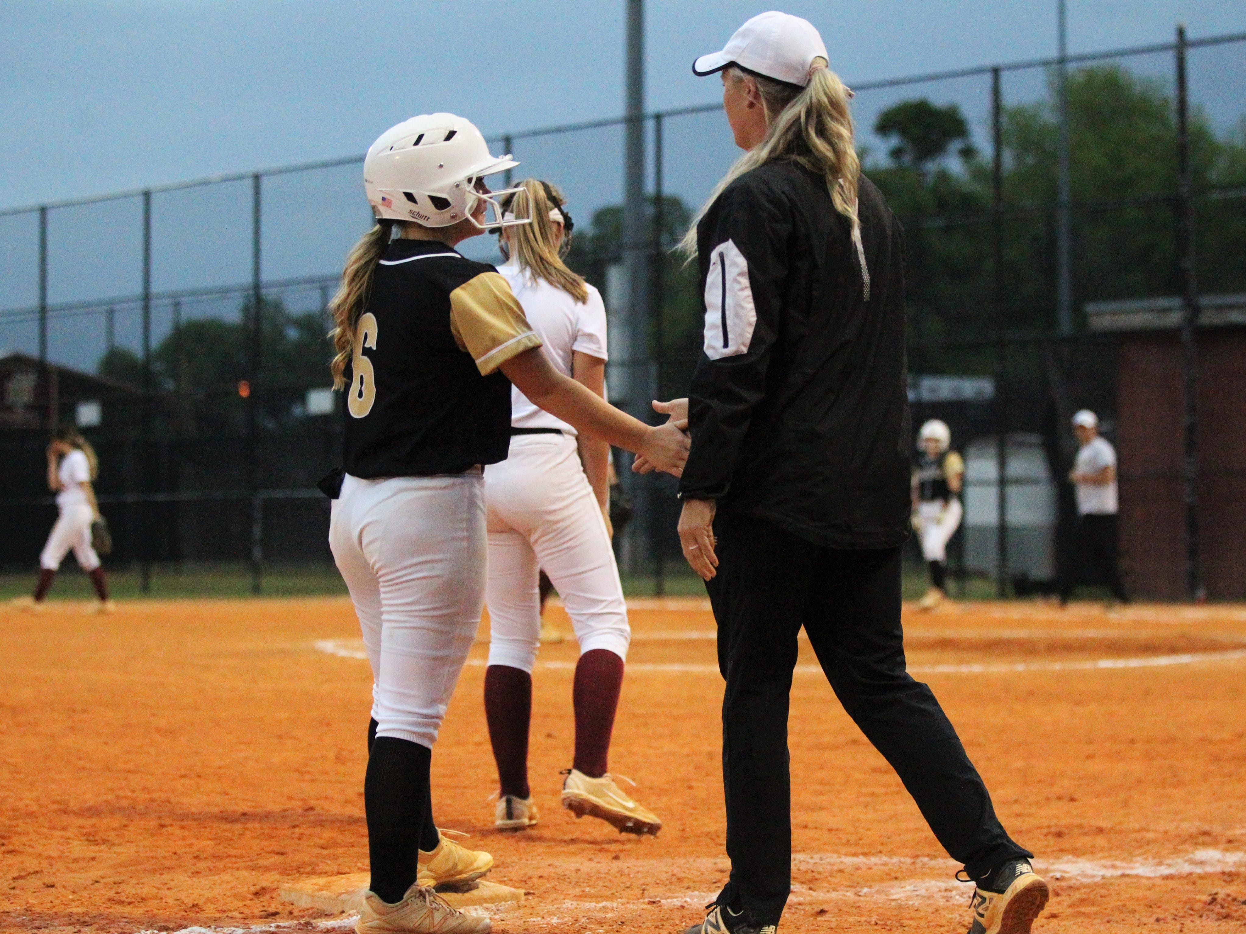 Lincoln softball coach Terese Waltman slaps hands with senior Shelby Sloan as Lincoln's softball team beat Florida High 7-3 on Thursday, April 4, 2019.