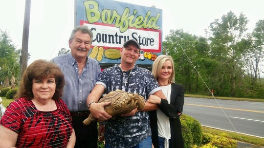 Clint Barfield holds Brook the tortoise outside the Barfield Country Store in Alford. Also pictured, from left, are his parents, Legatha and Eddie Barfield, and his wife, Rhonda Barfield.