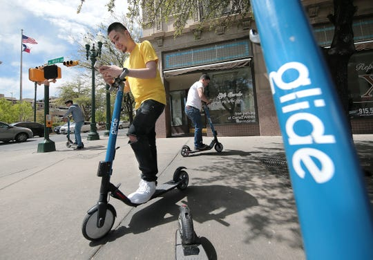 Brandon Garcia rents a Glide scooter Friday in downtown El Paso. The scooters, which can be seen throughout the city, can be rented through the Glide Your City app.