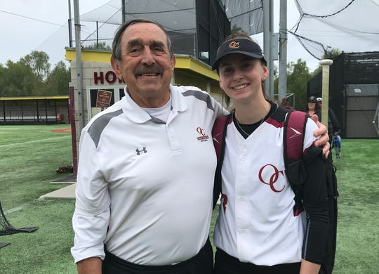 Head coach Pete Ackermann and pitcher Lexi Berg celebrate the Oaks Christian softball program's 500th program win on Thursday at home following a 1-0 victory over Newbury Park.