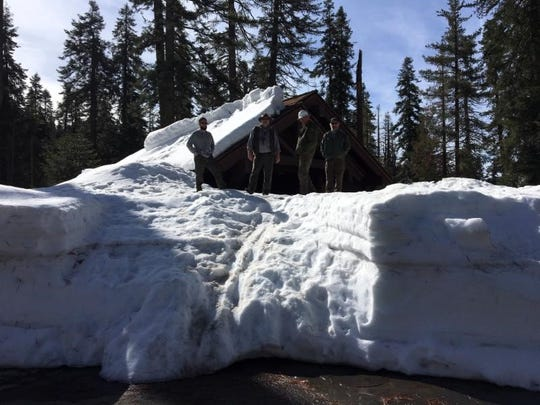 Rangers stand on the snow at the Sherman Tree comfort station.