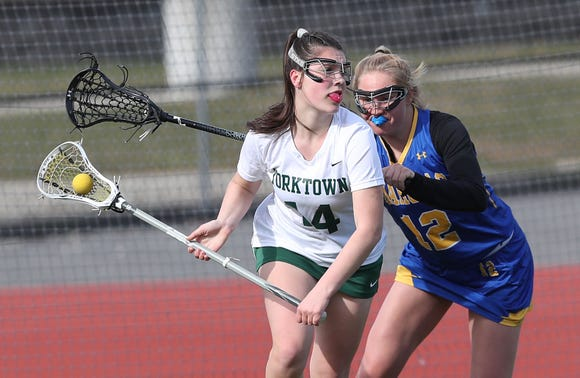Yorktown's Alexa Borges (14) tries to get around Mahopac's  Katrina Kidder (12) during girls lacrosse action at Yorktown High School April 4, 2019. Yorktown won the game 14-4.