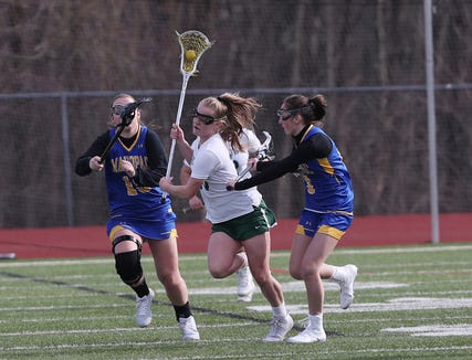 Yorktown's Kelsey McDonnell (15) gets between Mahopac's Katie McDonough (15)  and GiGi Genovese (6) as she moves the ball up the field during girls lacrosse action at Yorktown High School April 4, 2019. Yorktown won the game 14-4.