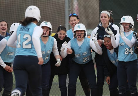 John Jay (EF) players wait at home plate for teammate Madison Mason after she hit a solo home run against Yorktown during softball action at Yorktown High School April 4, 2019. John Jay won the game 17-0.