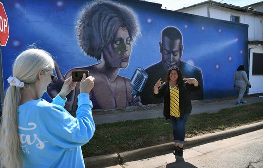 Patty Faulkner takes a photo of Nancy Esquivel in front of the new 36-foot-long mural painted on the Felix Lister Elks Lodge #1217 at 811 Homes Avenue.