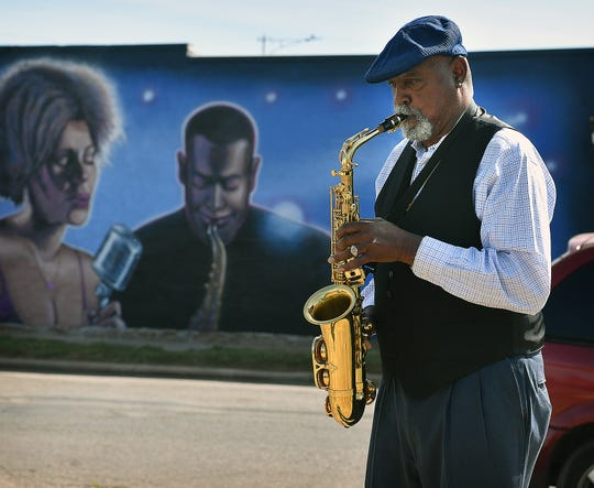 Saxaphonist Rickey Hickmon plays Friday morning during the unveiling of a mural at 811 Homes Avenue. The work was painted by Ralph Stearns and reflects the rich history of music from the east side of Wichita Falls.