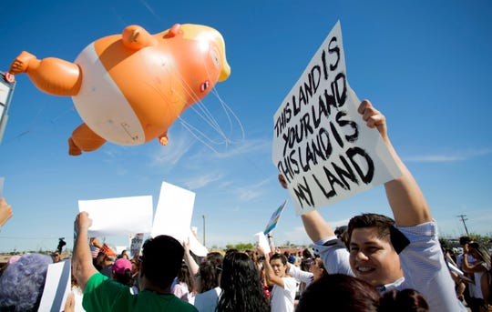 "A ""baby trump"" balloon flies above the Binational March of Unity in Calexico, Calif. during President Donald Trump's visit to the border town on April 5, 2019."