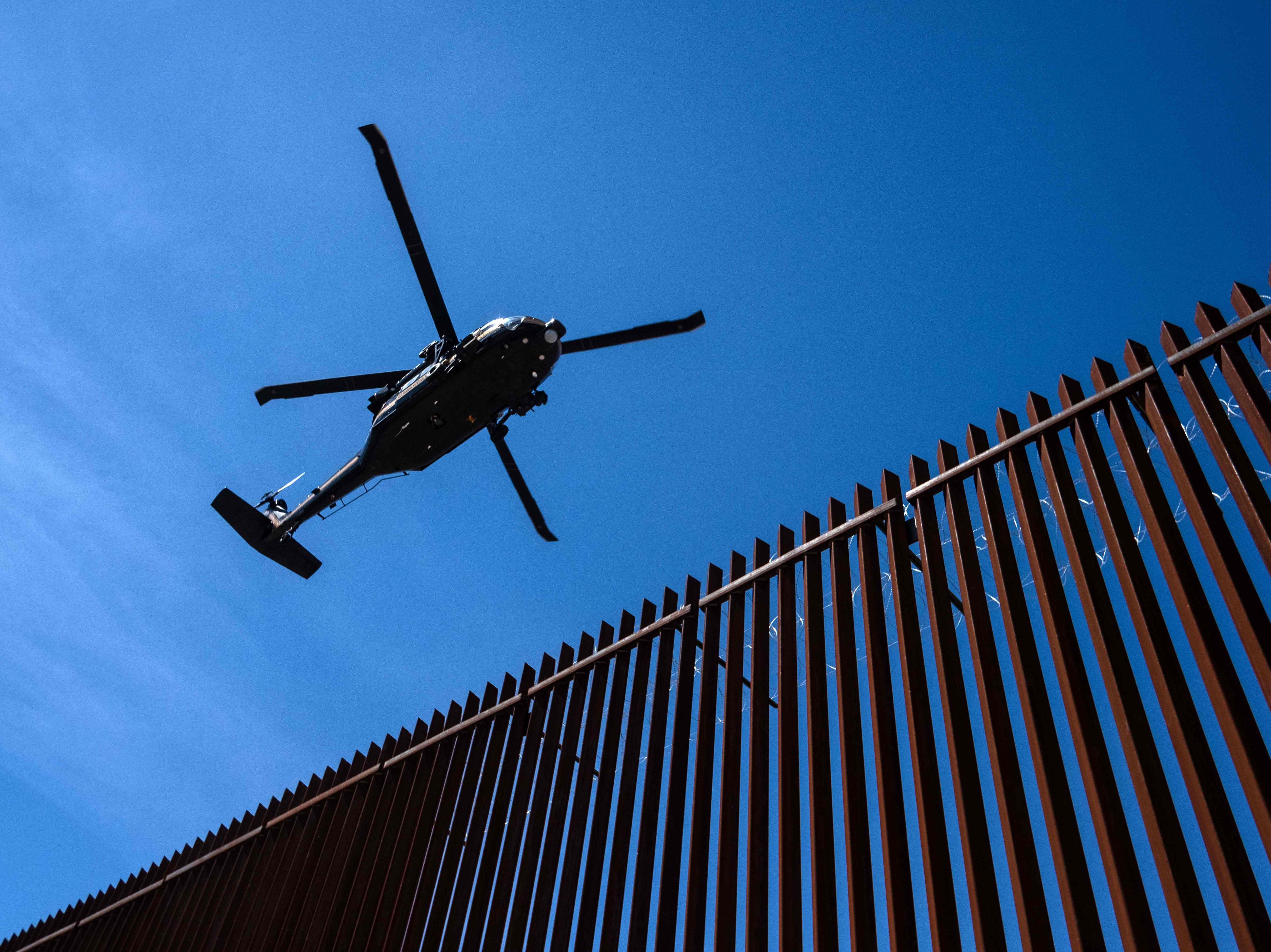 A US border patrol helicopter overflies the US-Mexico border fence as President Donald Trump visits Calexico, Calif., as seen from Mexicali, Baja California state, Mexico, on April 5, 2019.