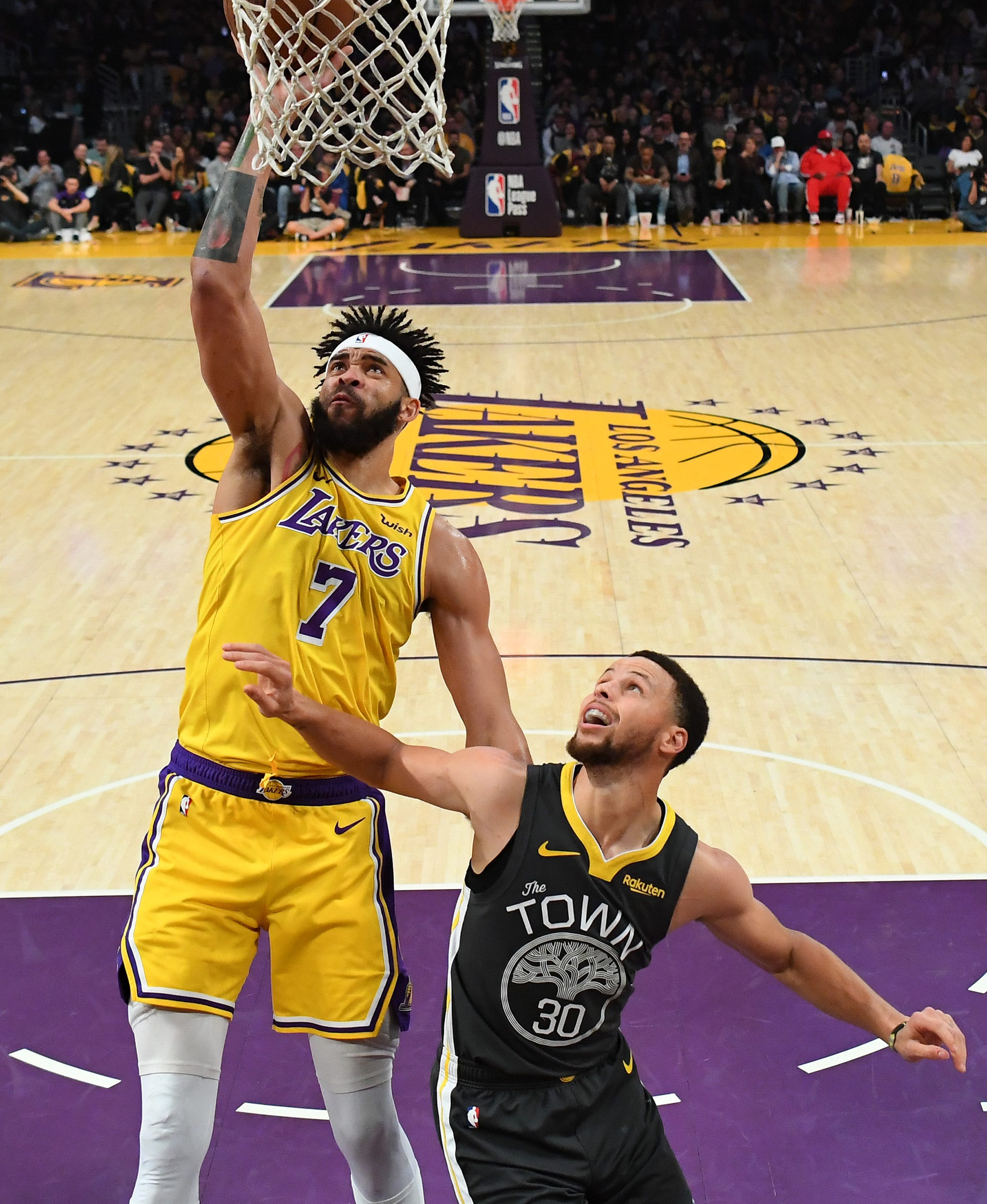 Alex Caruso dunks over Stephen Curry in a rare Lakers highlight Thursday.
