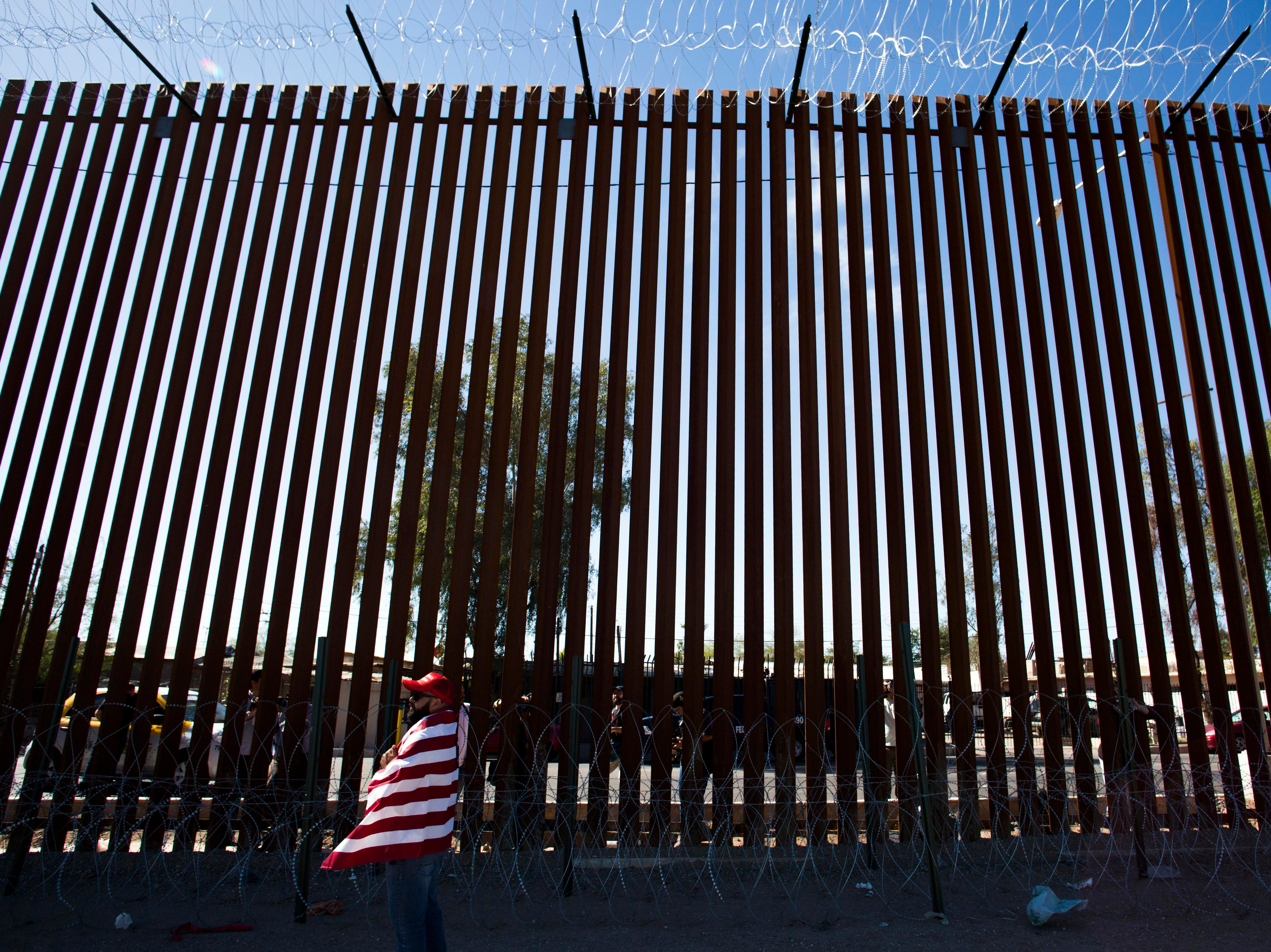 Ed Ramos, a trump supporter stands in front of the wall separating the U.S. and Mexico during President Donald Trump's visit to the border town of Calexico, Calif.