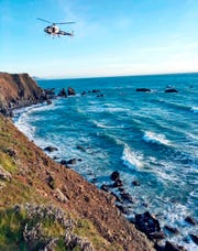 In this March 27, 2018, file photo provided by the California Highway Patrol a helicopter hovers over steep coastal cliffs near Mendocino, Calif., where a vehicle, visible at lower right, plunged about 100 feet off a cliff along Highway 1, killing all passengers.